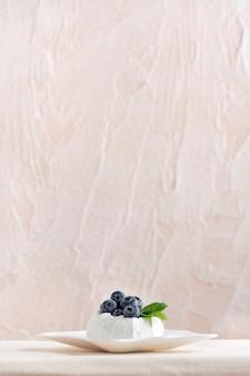 Deser jagodowy na spodku. beza ze świeżymi jagodami. widok z boku, jasne tło. rama pionowa.