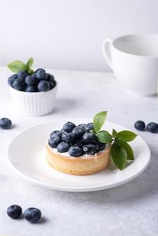 Deser jagodowy, pyszna tarta z jagodami na białym talerzu z zieloną gałązką na białym tle, zapiekane danie.