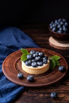 Deser jagodowy, tarta jagodowa na ciemnym tle drewnianych, letnie słodkie jedzenie.