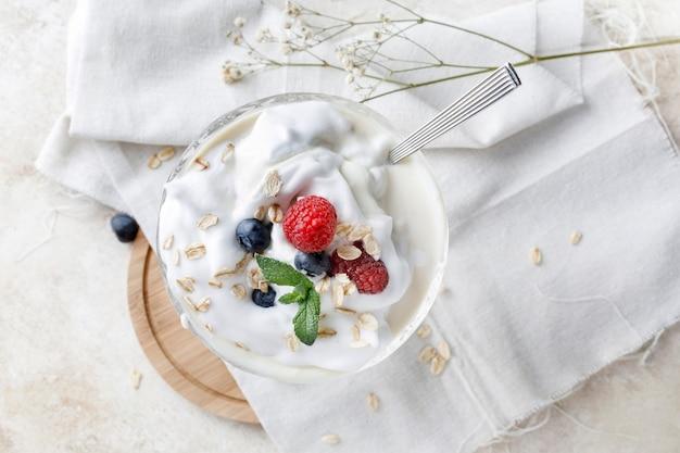 Deser jogurtowy z płatkami owsianymi, jagodami, maliną i miętą