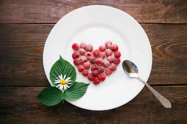 Deser malinowy z cukrem pudrem na talerzu. znak miłości
