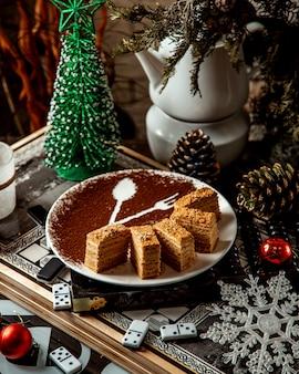Deser miodu pokrojony na talerzu z rysunkiem kakao