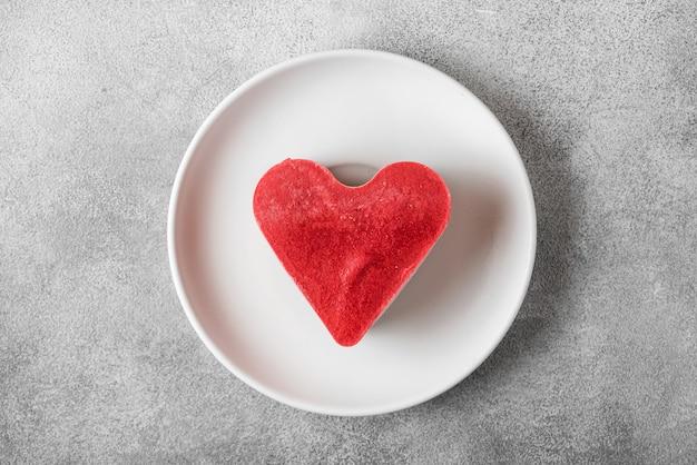 Deser na walentynki. surowe wegańskie ciasto w kształcie serca w talerzu. zdrowe pyszne jedzenie. widok z góry