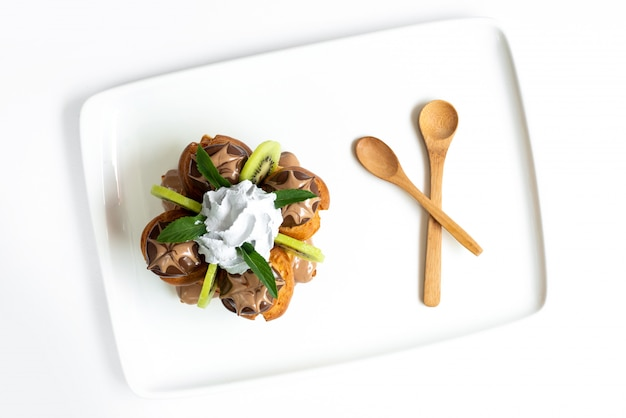 Deser owocowy z widokiem z góry zaprojektowany z małych ciastek z pokrojonymi kiwi i kremem na białym biurku wraz z drewnianymi łyżkami słodkie lody