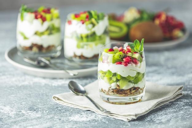 Deser parfait z kiwi w szkle ze składnikami. jogurt, muesli i owoce. zdrowa przekąska lub śniadanie. jasnoszara powierzchnia betonu.