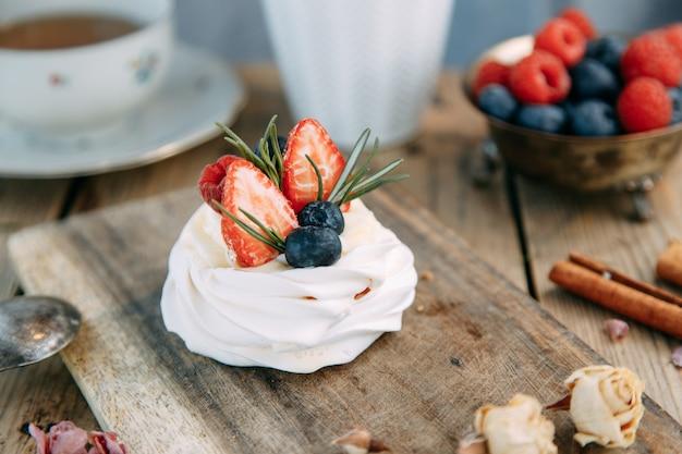 Deser pavlova z truskawkami i jagodami na drewnianym tle słodkie jagody bezowe