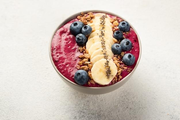 Deser śniadaniowy w misce z plastrami banana i jagodami