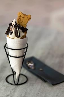Deser stożek lody z ciasteczkami kreatywnych dekoracji polewa na tle niewyraźne światło kopii.