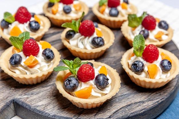 Deser tartaletki z owocami i jagodami, dobrane na drewnianej tacy
