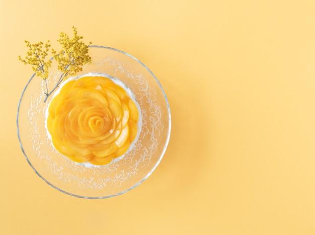 Deser trzy mleka ozdobiony brzoskwiniami na żółtym tle. skopiuj miejsce. widok z góry.