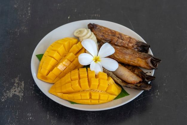 Deser w stylu tajskim, żółte mango z lepkim ryżem bananowym w liściach palmowych. żółte mango i lepki ryż to popularne tradycyjne potrawy tajlandii. ścieśniać