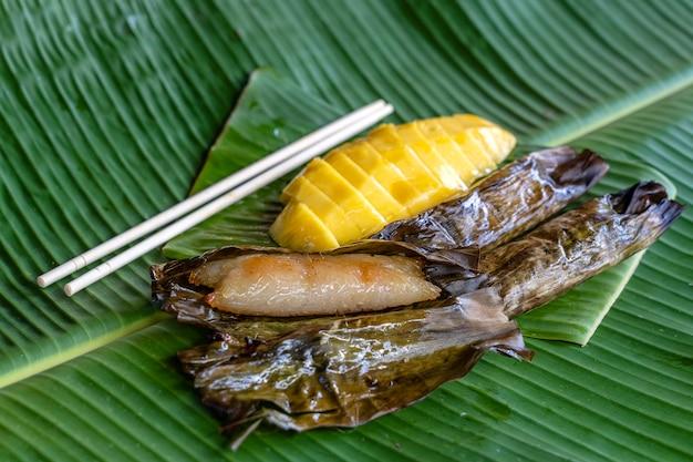 Deser w stylu tajskim, żółte mango z lepkim ryżem bananowym w liściach palmowych. żółte mango i lepki ryż to popularny tradycyjny deser tajlandii. ścieśniać