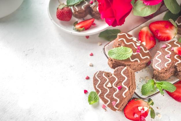 Deser walentynki. czekoladowe mini ciastka biszkoptowe w kształcie serca z truskawkami i miętą. widok z góry
