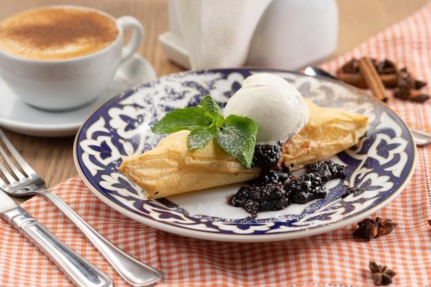 Deser z ciasta francuskiego z konfiturą jagodową i kulką lodów waniliowych ozdobiony listkiem mięty w talerzu z tradycyjnym uzbeckim