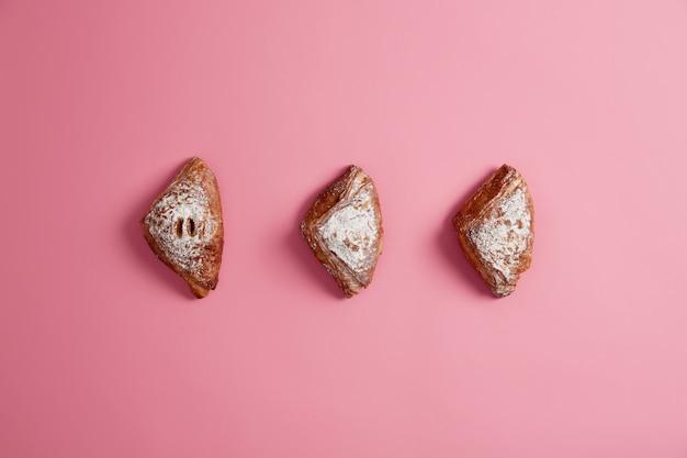 Deser z ciasta francuskiego z nadzieniem dżemowym i cukrem pudrem na bezproblemową różowym tle. pieczenie słodkich ciast do jedzenia. wyroby piekarnicze i cukiernicze. domowe jedzenie wysokokaloryczne. strzał z góry