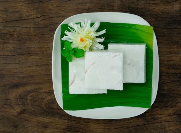 Deser z galaretką z mleka kokosowego ozdobiony bananem w białym talerzu na drewnianym tle widok z góry