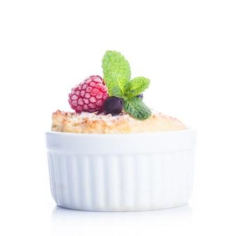 Deser z jagodami i miętowym wystrojem w białym raclette na białym tle