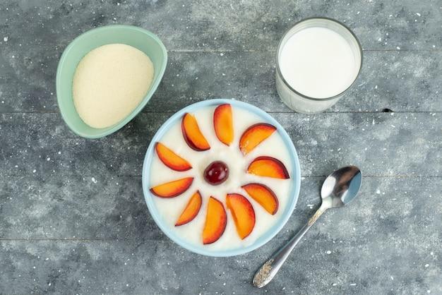 Deser z widokiem z góry z owocami pokrojonymi owocami na talerzu wraz z zimnym mlekiem na niebiesko