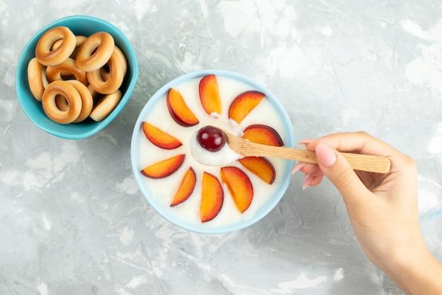 Deser z widokiem z góry z owocami pokrojonymi owocami na talerzu wraz ze słodkimi krakersami na szaro