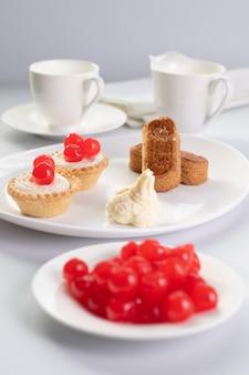 Deser ze słodkich chrries z paluszkami migdałowymi i dwoma ciastami w koszyku oraz filiżanką kawy i dzbankiem na mleko w tle