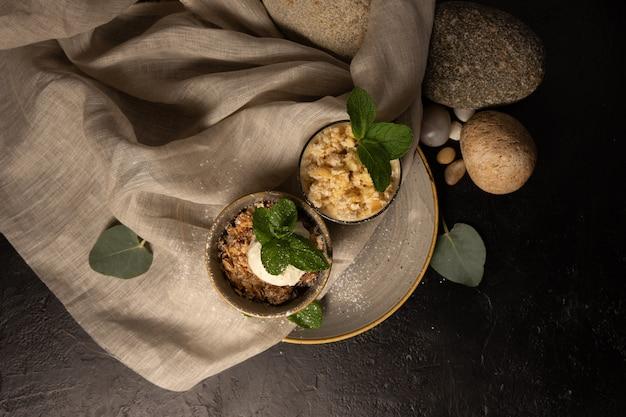 Deserowa granola z gałką lodów waniliowych ozdobiona listkami mięty. deser twarogowy z jogurtem w przezroczystej szklance