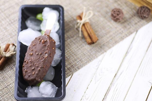 Deserowe lody czekoladowe z orzechami na drewnianym patyczku