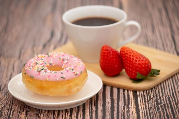 Deserowe pączki, truskawki i filiżankę gorącej kawy na drewnianym stole