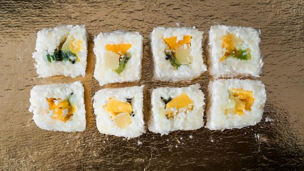 Deserowe sushi - rolka z różnymi owocami i serem śmietankowym w środku. na złotym tle