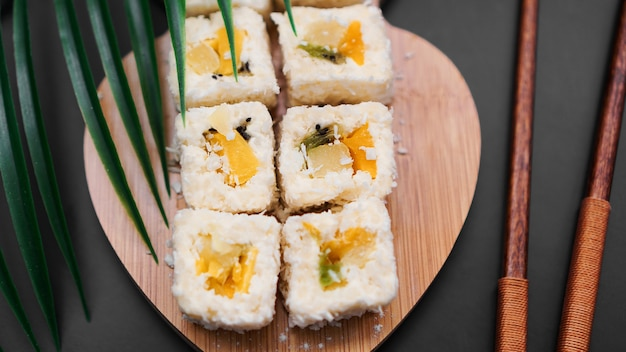 Deserowe sushi. słodkie kiwi, ananasowe sushi. sushi na drewnianej tacy na czarnym tle z tropikalnym liściem