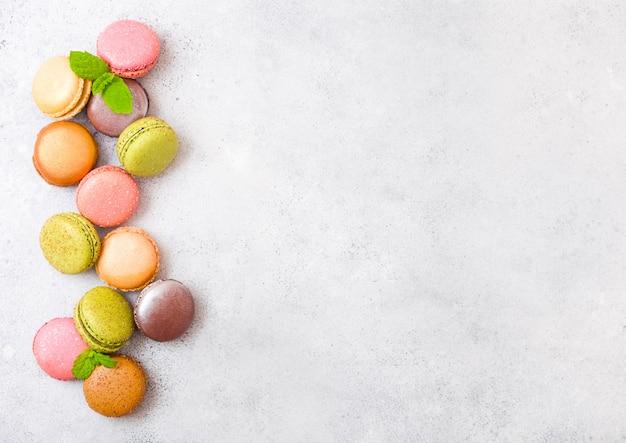Deserowy macaron lub macaroon tortowy liść z menniczym liściem na kamiennym kuchennym stole. widok z góry.