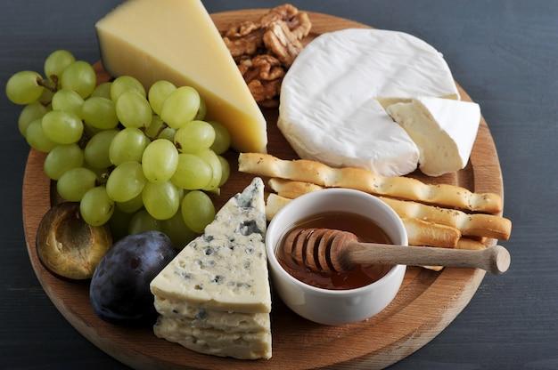 Deserowy ser, paluszki chlebowe, miód, orzechy i winogrona