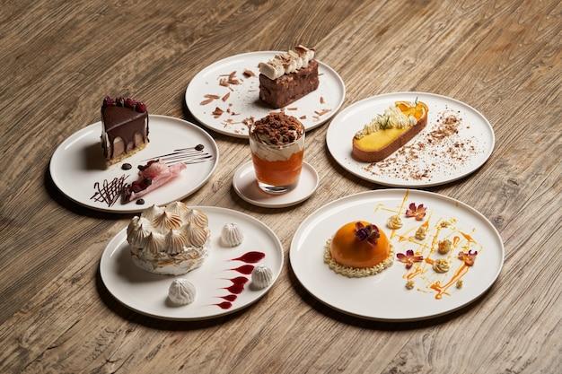Deserowy stół z babeczką, musem, ciastkami, sernikiem. kawałek ciasta na białym talerzu na tle drewniany stół