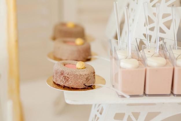 Desery z owocami, mus, herbatniki. różne rodzaje słodkich wypieków, małe kolorowe słodkie ciasta, macaron i inne desery w słodkim bufecie. batonika na urodziny.