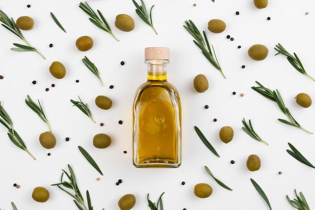 Design z liśćmi i oliwkami wokół butelki z olejem