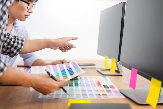 Designer editor w pracy rysuje szkice nowego projektu na tablecie graficznym i palecie kolorów
