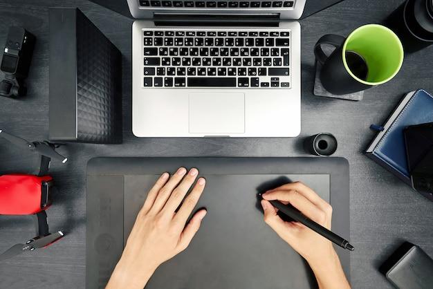 Designerskie biurko z soczewkami, dronem i mężczyzną pracującym na tablecie rysunkowym