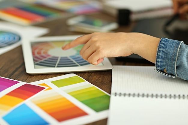 Designerskie miejsce pracy. kobieta za pomocą tabletu