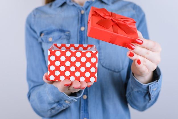 Desire romantyczna zabawa radość kamera czapka boże narodzenie nowy rok walentynki przyjaciel rodzina mały ty osoba ludzie koncepcja wieku nastolatków. przycięte zdjęcie z bliska prezent na białym tle na szarej ścianie