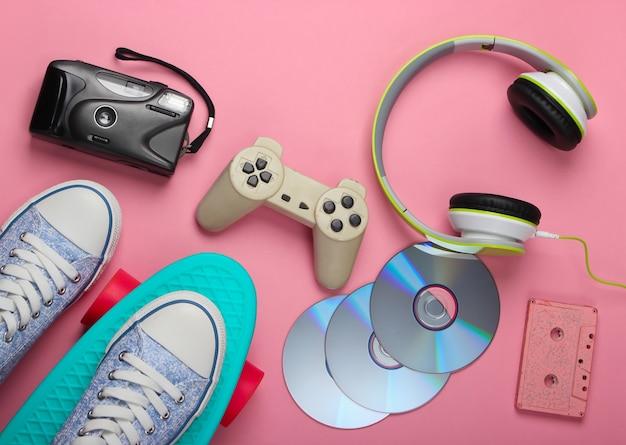 Deska cruiser, słuchawki stereo, kaseta magnetofonowa, płyty cd, kamera retro na różowej powierzchni