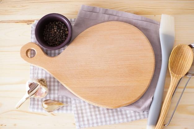 Deska do krojenia drewniana i ręcznik na podłoże drewniane, miejsca na tekst. leżał na płasko.