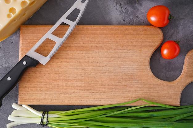 Deska do krojenia drewniana i różne warzywa na szarym tle, miejsca na tekst. leżał na płasko. zbliżenie