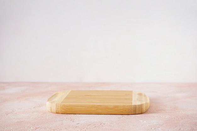 Deska do krojenia drewniana na beżowym tle z miejscem na tekst.