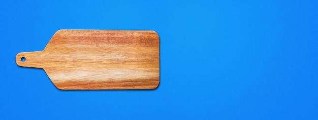 Deska do krojenia drewniana na białym tle na niebieskim tle. baner poziomy