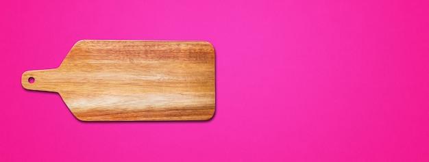 Deska do krojenia drewniana na białym tle na różowym tle. baner poziomy