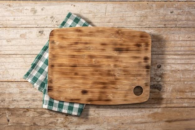 Deska do krojenia makieta i zielony obrus na drewnianym stole
