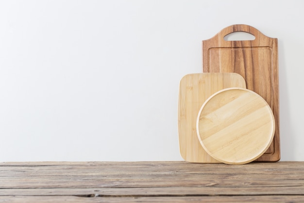 Deska do krojenia na drewnianym stole na tle białej ściany