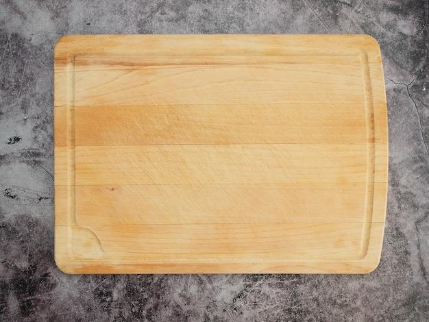 Deska do krojenia na stole z szarego marmuru.