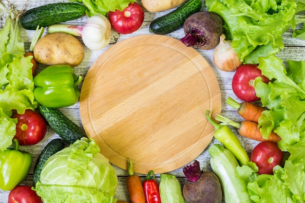 Deska do krojenia okrągła i warzywa. zdrowe odżywianie. tło copyspace