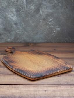 Deska do krojenia przy drewnianym stole, z teksturą tła ściany