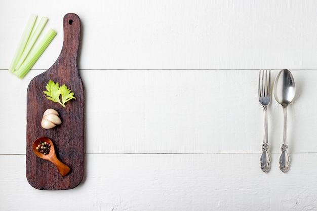 Deska do krojenia, przyprawa i sztućce na białym drewnianym